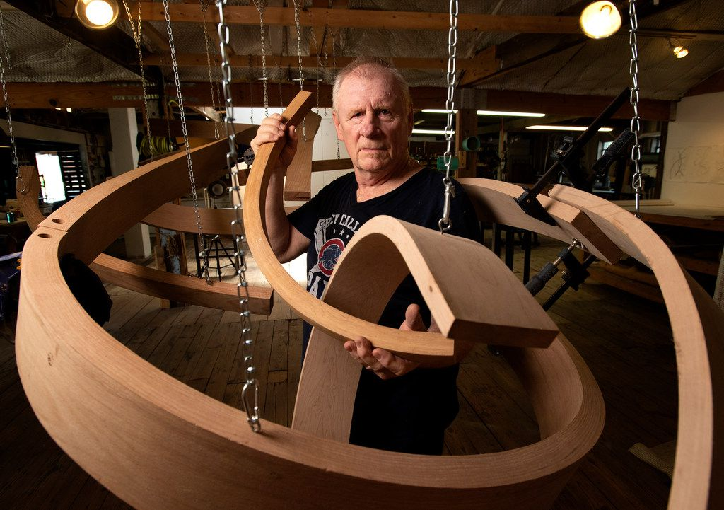 Wood sculptor Rick Maxwell poses with an unfinished sculpture at his studio in The Cedars neighborhood in Dallas.