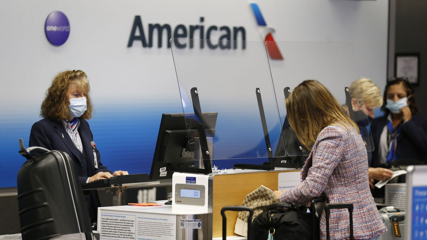 An American Airlines agent tends to customers in Terminal C at DFW International Airport on Tuesday, July 21, 2020. The pandemic has reduced the amount of travel at the airport. (Vernon Bryant/The Dallas Morning News)