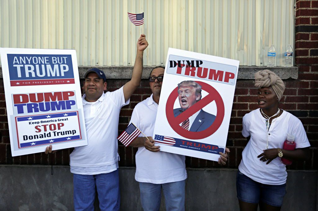 (From left) Raul Torres, Atilano Platas and a woman who gave her name as LaTavya F protest before a rally for presumptive Republican presidential nominee Donald Trump Thursday, June 16, 2016 at Gilley's in Dallas. (G.J. McCarthy/The Dallas Morning News)