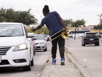Joshua Reese, 23, accepts a tip while performing his trombone close to the intersection of North Cockrell Hill Road and DFW Turnpike on Tuesday, Oct. 26, 2021, in Dallas. Reese has been performing for nine years as a way to raise money to take care of his mom and himself. (Juan Figueroa/The Dallas Morning News)