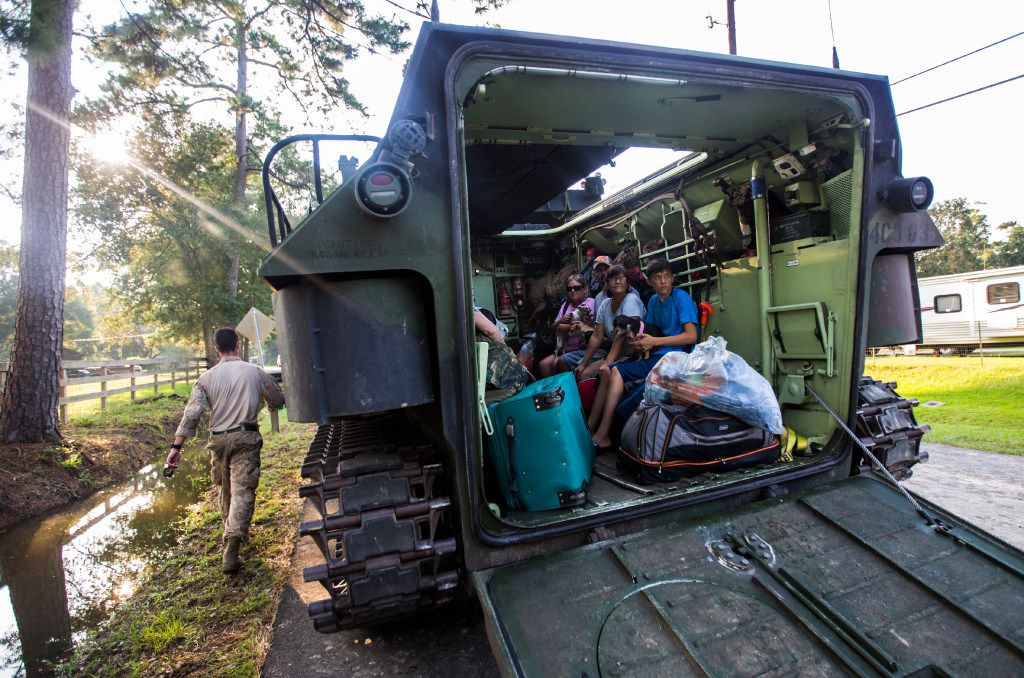 Evacuees from the Cooks Lake Road area sit in the back of a Marine amphibious assault vehicle after being removed from areas flooded as a result of Tropical Storm Harvey on Thursday, August 31, 2017 near Lumberton, Texas. (Ashley Landis/The Dallas Morning News)