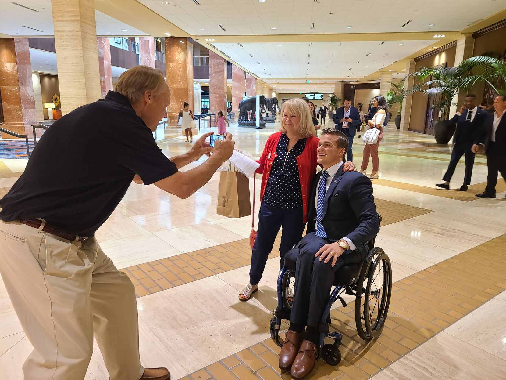 Debbie Billingsly of Van Alstyne poses with Rep. Madison Cawthorn, R-N.C., during the Conservative Political Action Conference in Dallas as her husband, Paul Billingsly, snaps the photo. Cawthorn suggested the Biden administration's a door-to-door campaign to expand COVID-19 vaccination was a dry run for a government scheme to confiscate Bibles and guns.