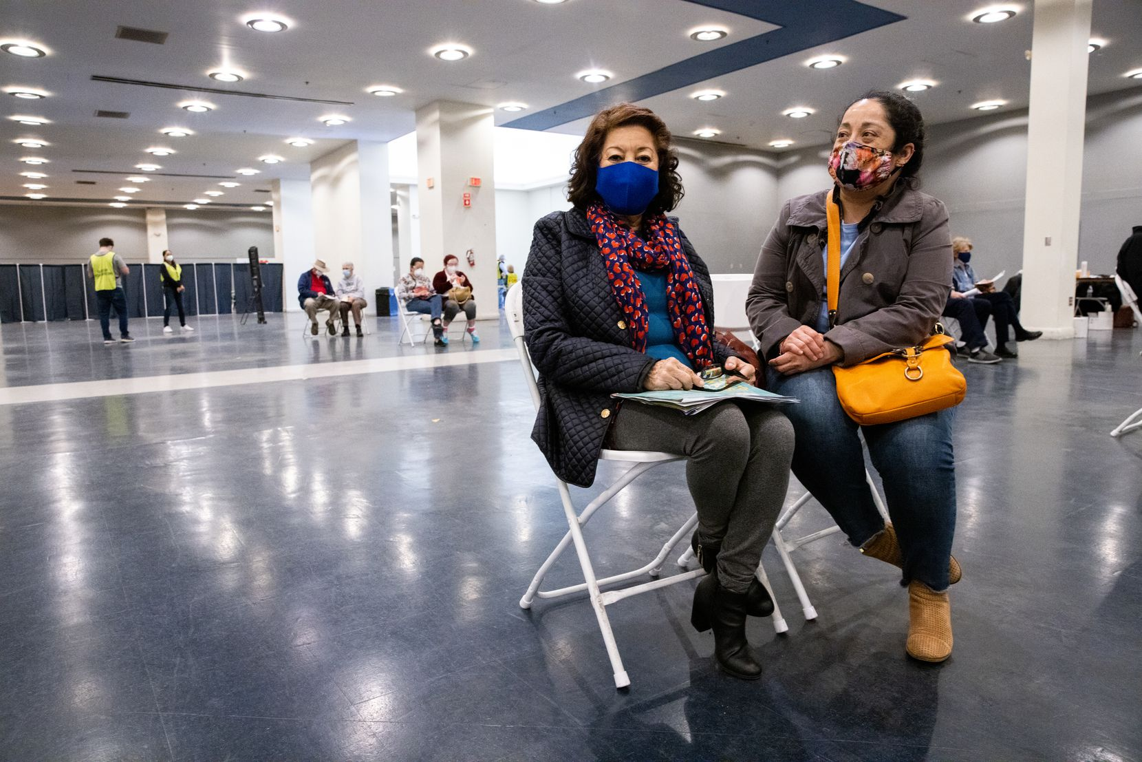 María Dolores Sanchez (left) sits with daughter Cynthia Tort-Urbina in the post-vaccination waiting area at Fair Park in Dallas on Tuesday afternoon, Feb. 2, 2021. (Juan Figueroa/ The Dallas Morning News)