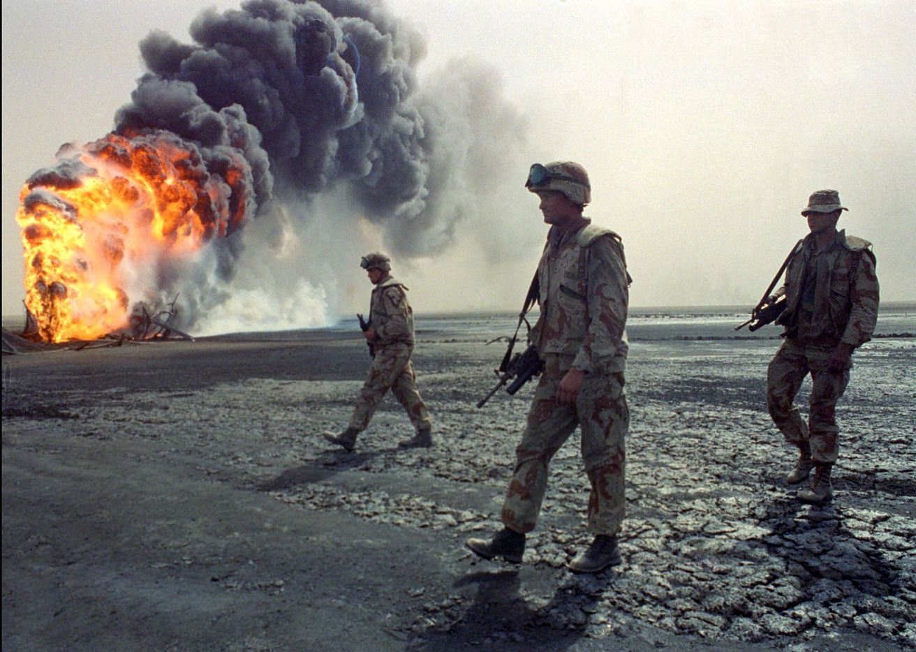 A U.S. Marine patrol walks across the charred oil landscape near a burning well  during perimeter security patrol near Kuwait City on March 7,  1991, during the Gulf War that ended the Iraqi  occupation of Kuwait.