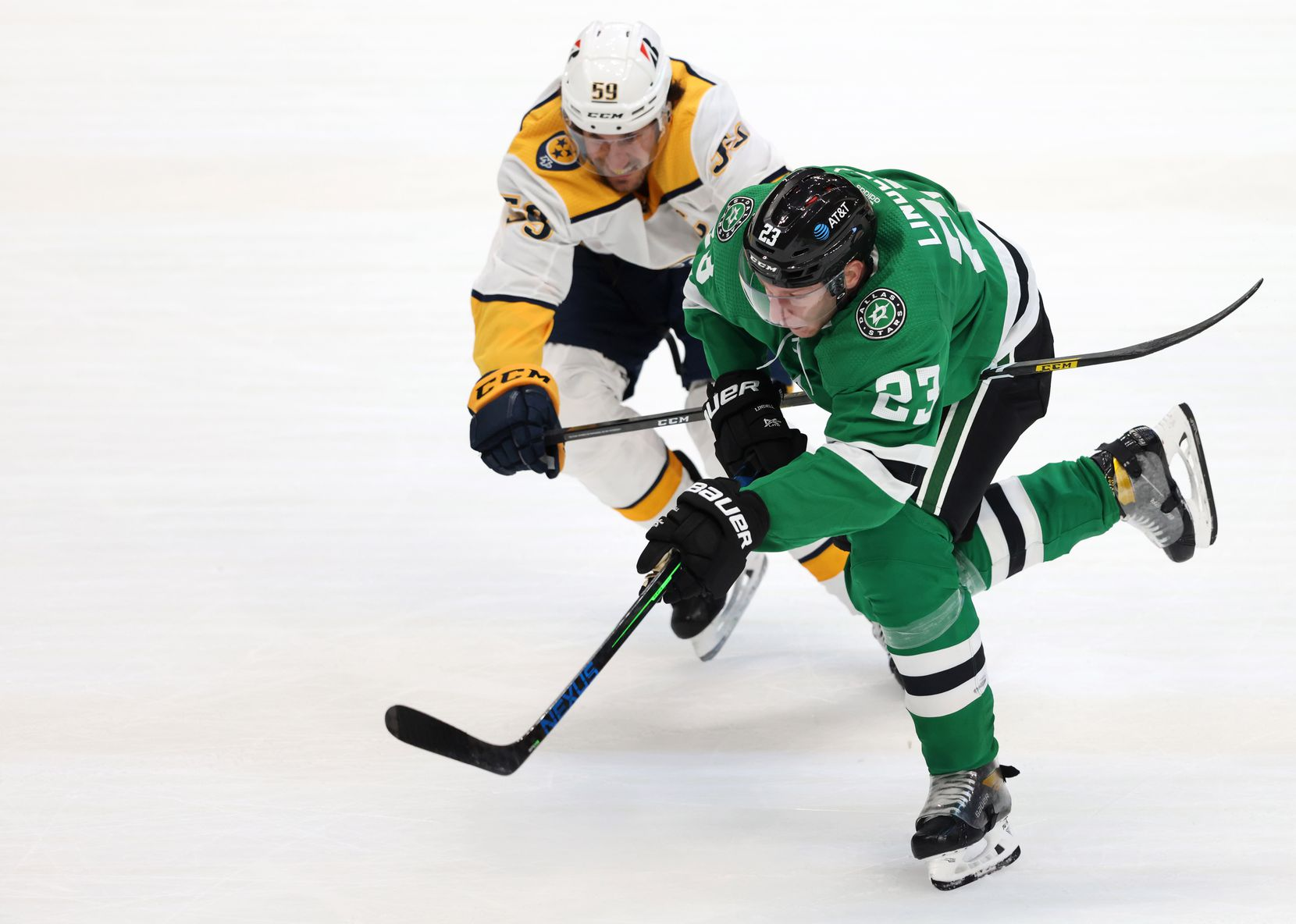 Dallas Stars defenseman Esa Lindell (23) races towards the puck as he is defended by Nashville Predators defenseman Roman Josi (59) during the second period of play in the Stars home opener at American Airlines Center on Friday, January 22, 2021in Dallas. (Vernon Bryant/The Dallas Morning News)