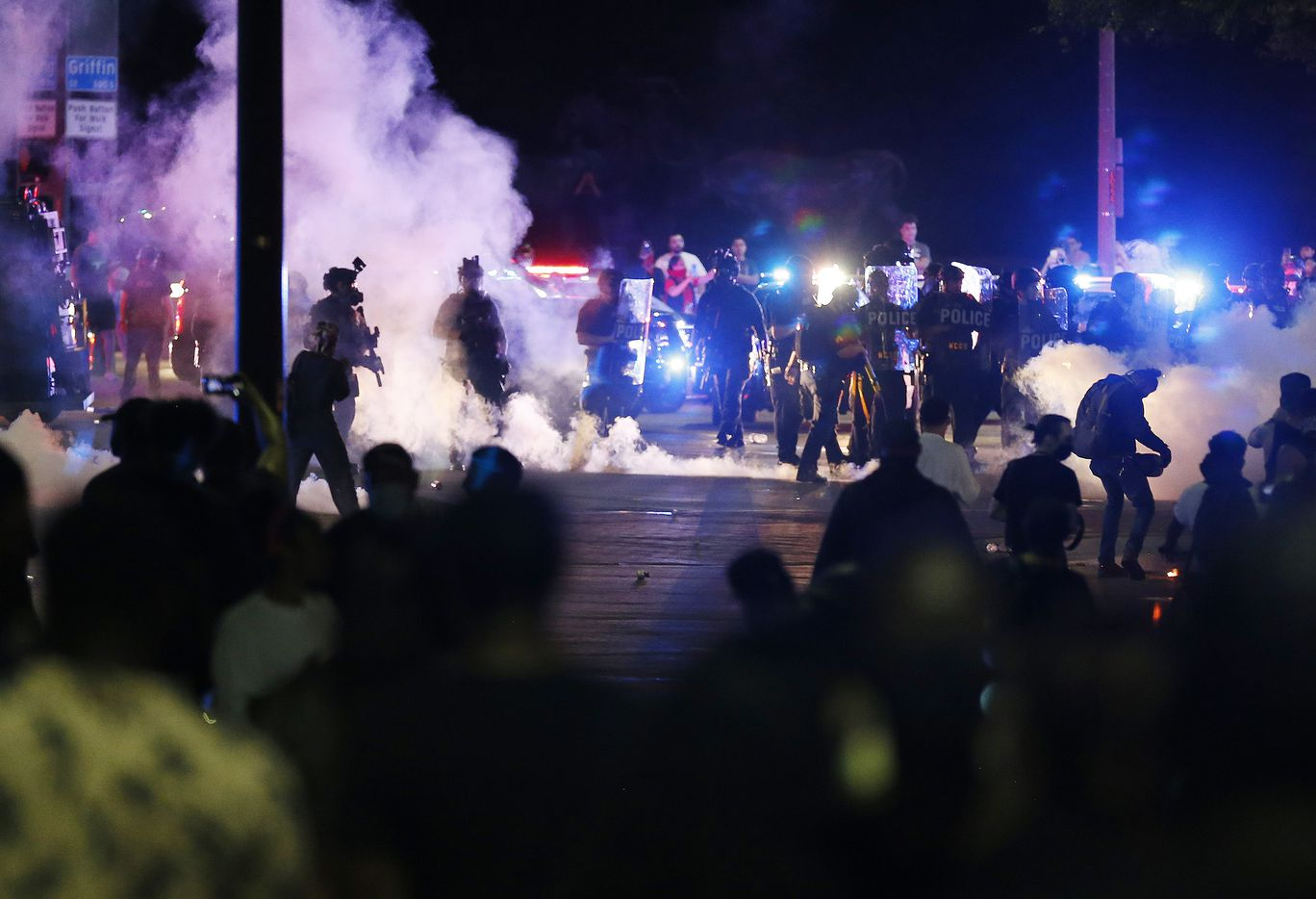 Tear gas fills the air as Dallas police attempt to disperse the crowd along Young Street and Griffin in downtown Dallas, on Friday, May 29, 2020. George Floyd died in police custody in Minneapolis on May 25.