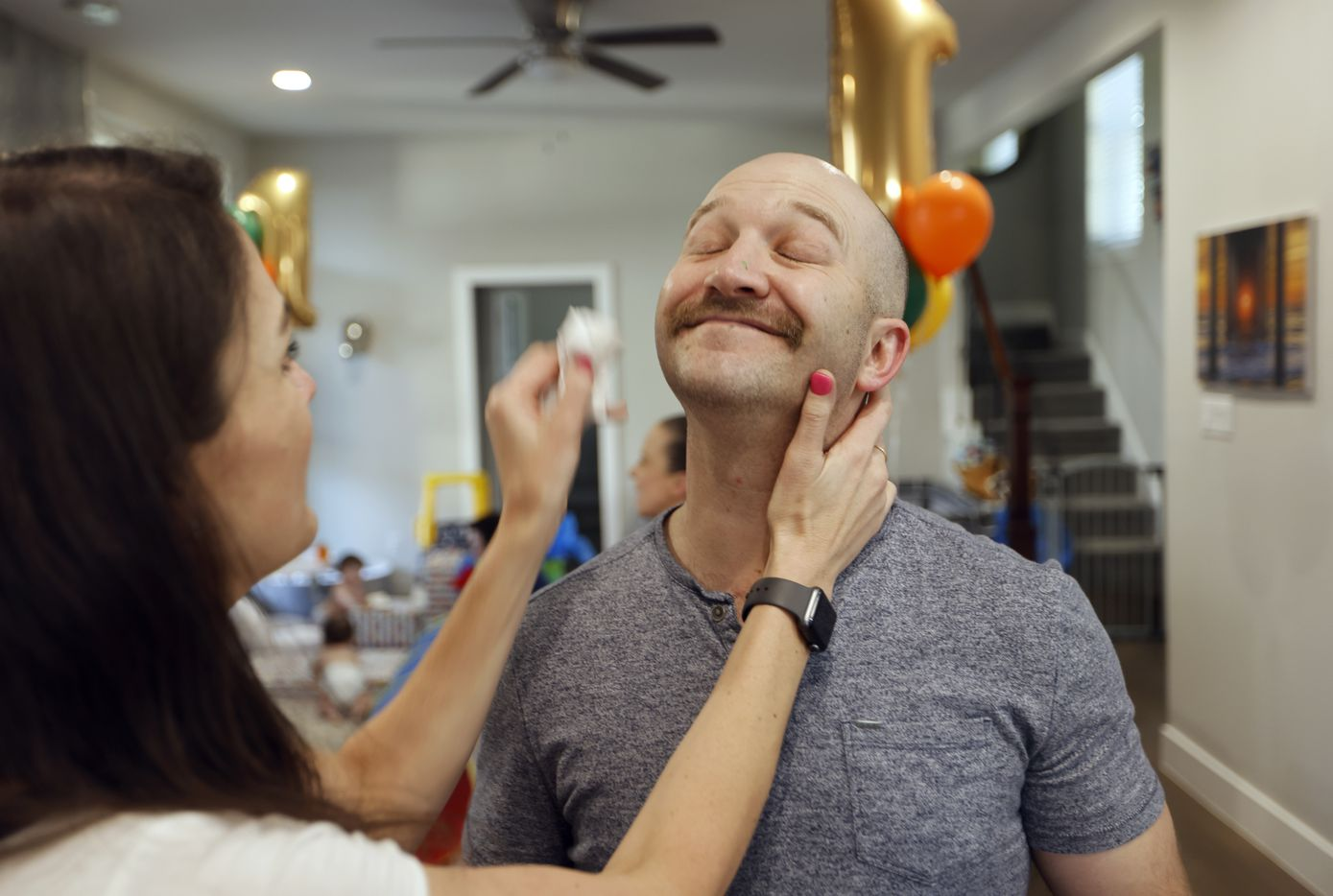 Jenny Marr wipes icing off the face of Chris Marr during their kid's one year birthday party at their home on Monday, March 15, 2021in Grapevine, Texas.