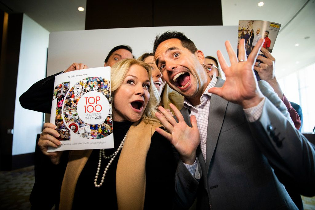 Employees of Fisher Investments posed in a photo booth with copies of the 2018 Dallas Morning News Top 100 magazine at the end of the annual luncheon.