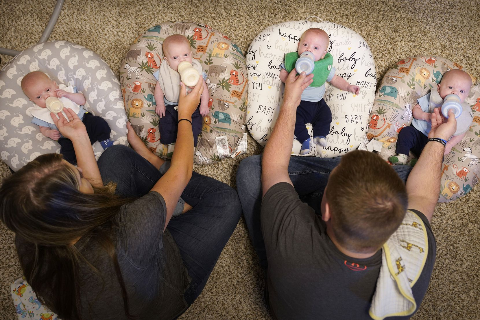 Katie and Chris Sturm feed quadruplets (from left) Hudson, Daniel, Austin and Jacob, who were born in July, on Tuesday, Sept. 29, 2020, in Haslet, Texas. (Smiley N. Pool/The Dallas Morning News)