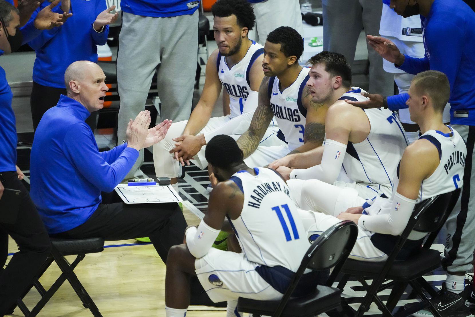 Dallas Mavericks head coach Rick Carlisle (left) encourages his players (from top), guard Jalen Brunson (13), guard Trey Burke (3), guard Luka Doncic (77), center Kristaps Porzingis (6) and forward Tim Hardaway Jr. (11) during a timeout in the fourth quarter of loss to the LA Clippers in Game 7 of an NBA playoff series at the Staples Center on Sunday, June 6, 2021, in Los Angeles.