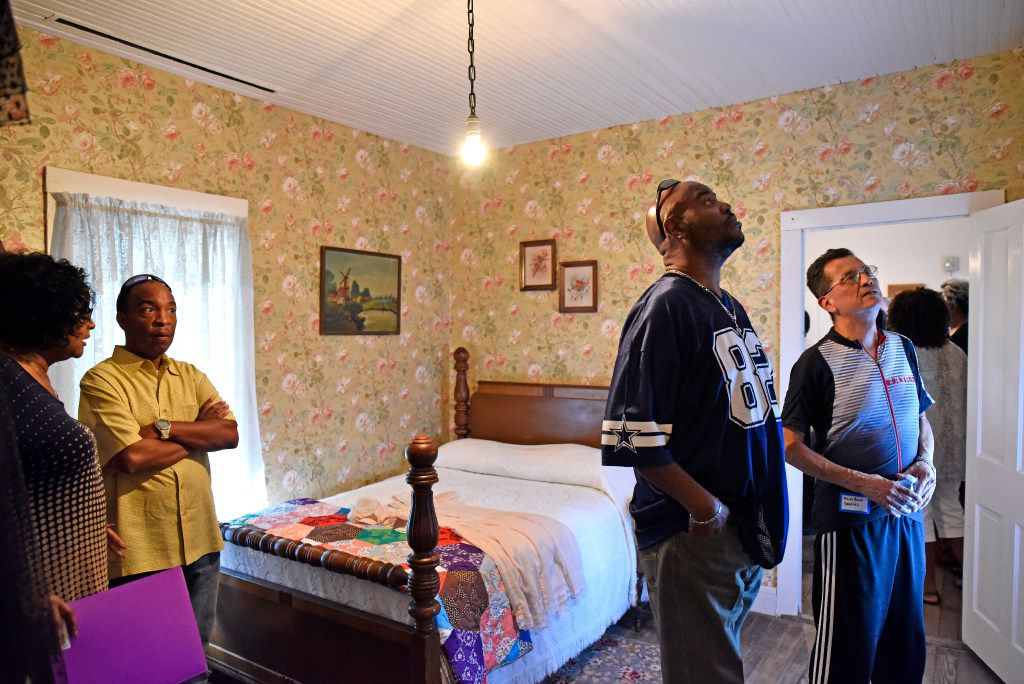 Far-left: Deborah Isaac Hopes, 65, vice president of Remembering Black Dallas, Inc., speaks with Greg Walker, 58, of Dallas, as they tour the inside of a shotgun house during the opening celebration of the new exhibit titled Neighborhoods We Called Home, at the Dallas Heritage Village near downtown Dallas, Thursday, Aug. 31, 2017. The bed photographed belonged to the grandparents of Deborah Isaac Hopes and is dated to be from the 1930s. The bed was donated for the exhibit. Ben Torres/Special Contributor