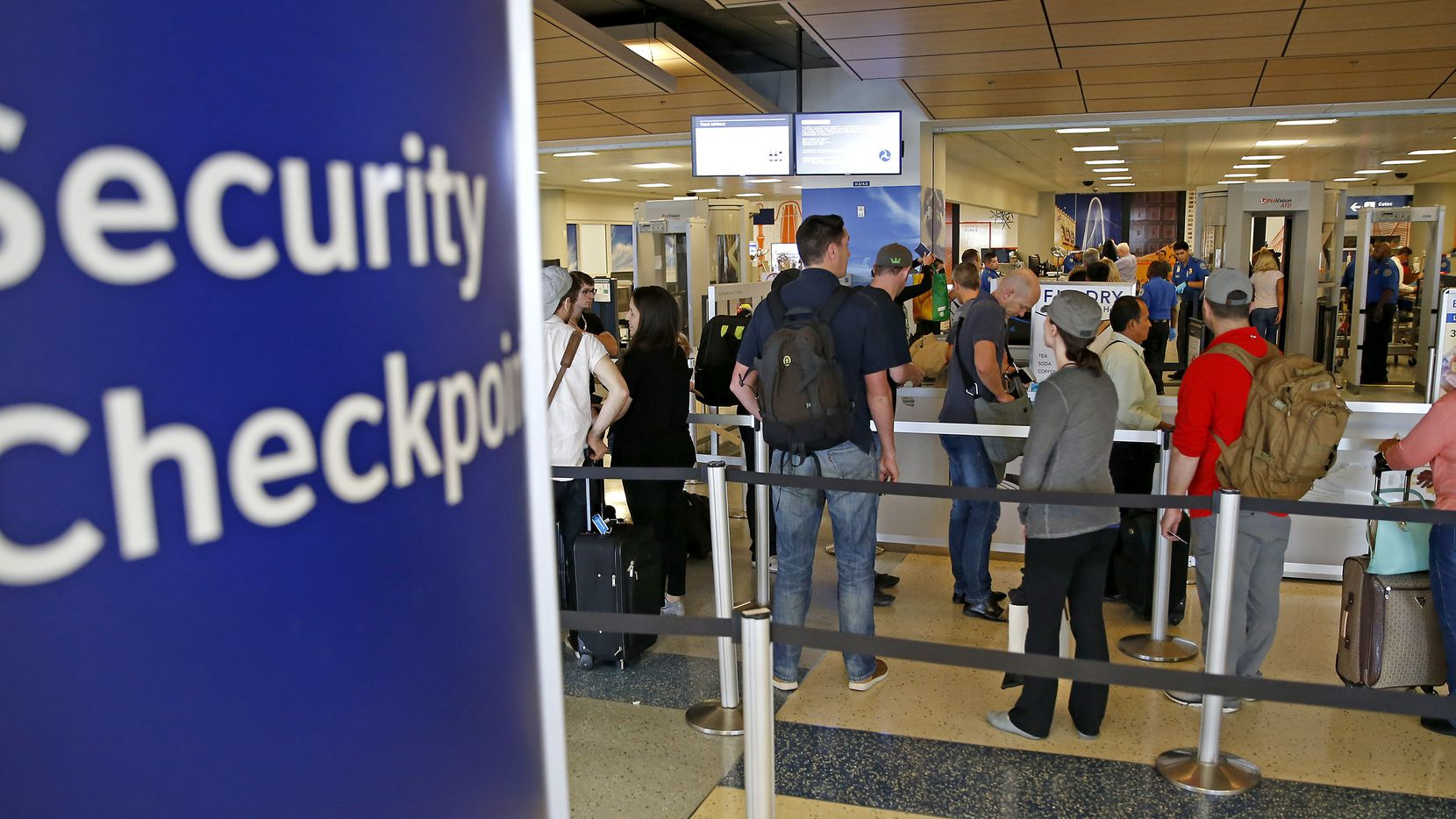Travelers wait to enter a TSA security checkpoint at DFW International Airport.