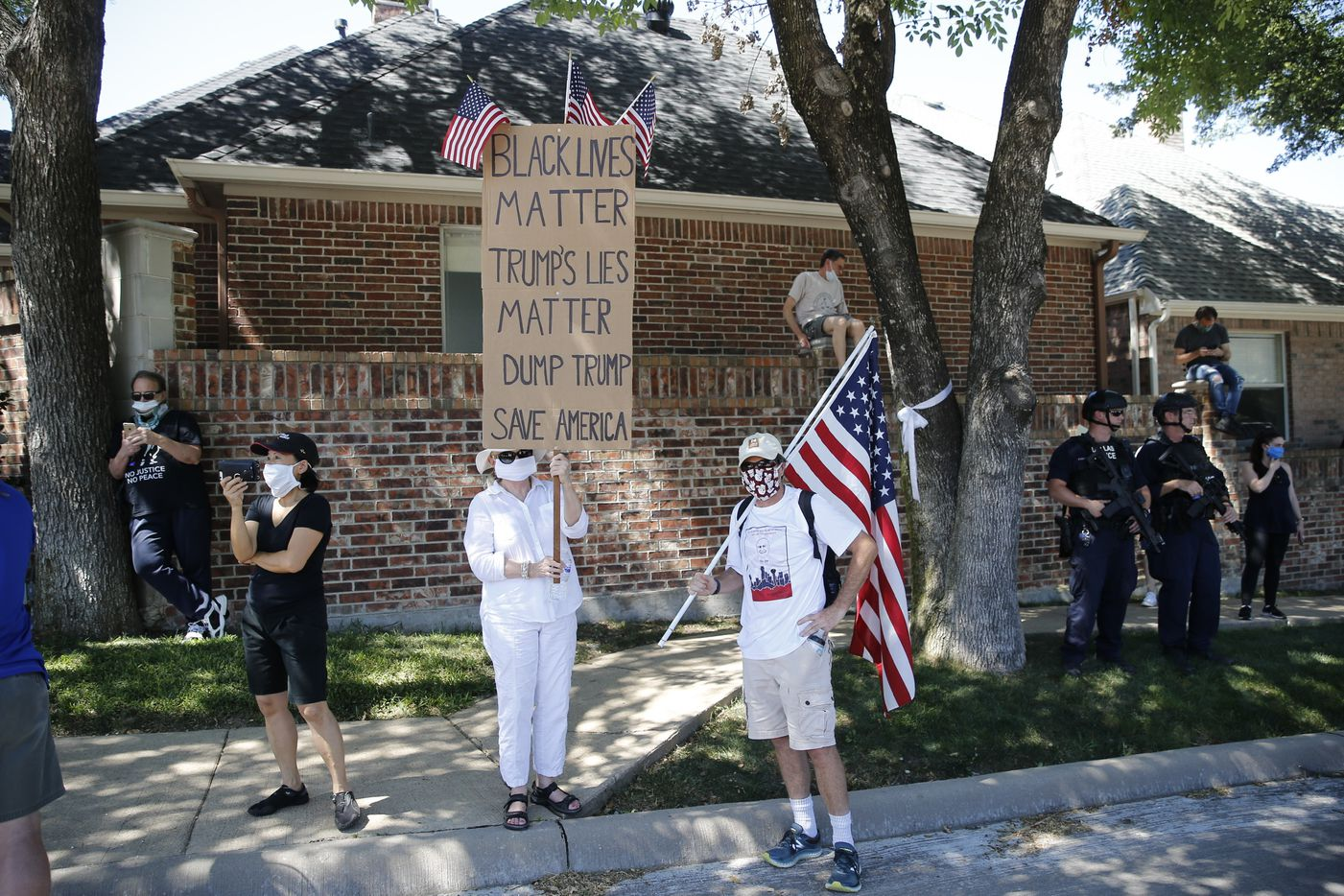 Anti-Trump protesters Dianne and Barry Smith, of Dallas, hold signs near Gateway Church in Dallas, on Thursday, June 11, 2020. President Donald Trump is in town for multiple events. (Vernon Bryant/The Dallas Morning News)