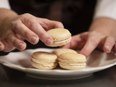 Andrea Meyer, of Bisous Bisous Patisserie, plates a group of churro-flavored macrons after demonstrating how she makes her recipe at her shop in Dallas.