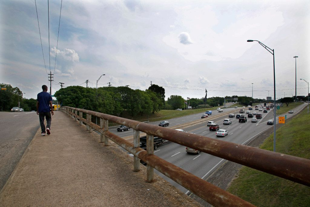 A pedestrian crosses the Ewing Street overpass as traffic from southbound I-35E exits at Marsalis Avenue in Dallas Wednesday, May 31, 2017. One of the plans for the proposed deck park would span from Ewing to Marsalis.