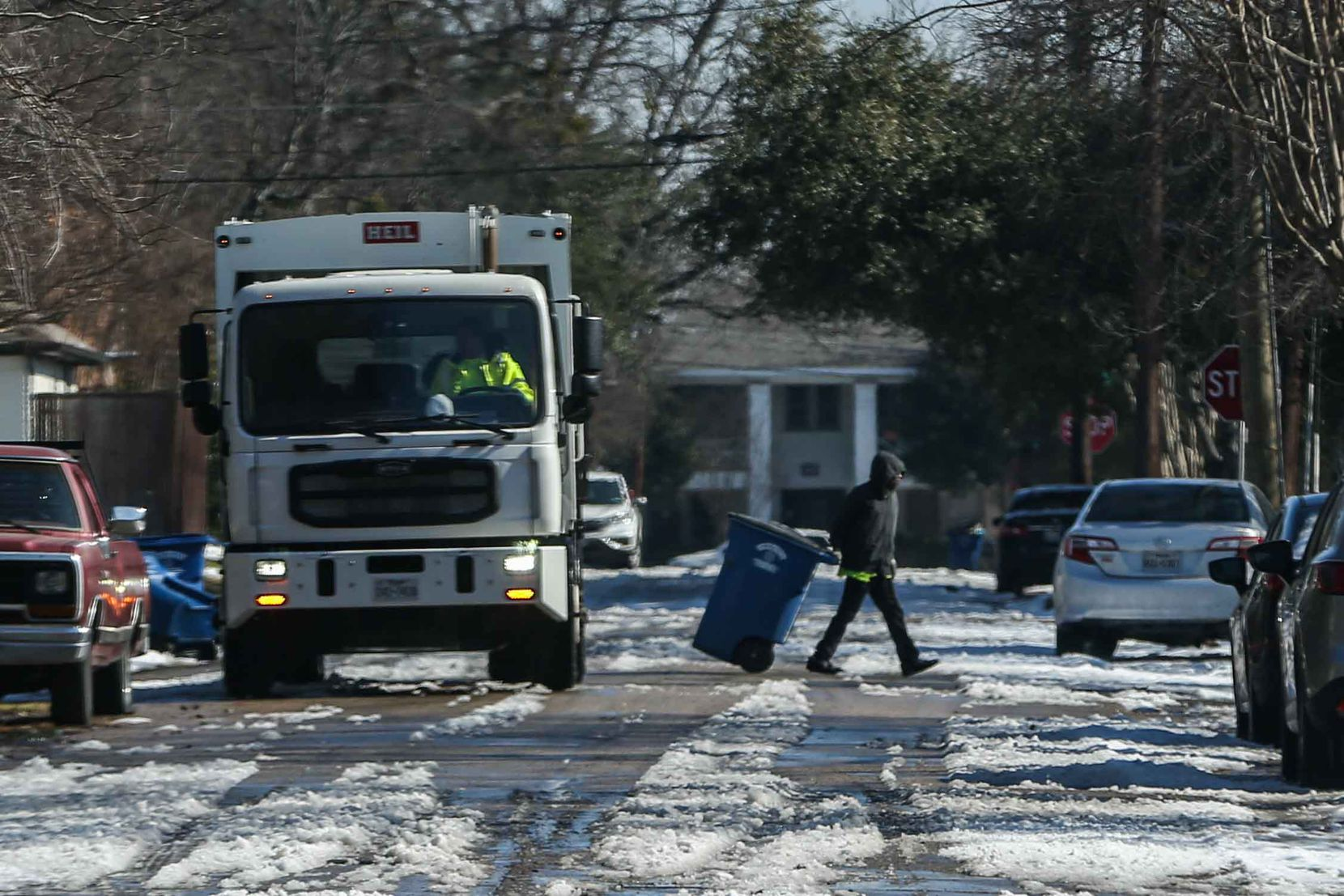 Garbage collection service continues its work around the city as temperatures start to rise and the snow accumulated after the passage of the snowstorm begins to melt on Worth Street in Dallas on Friday, Feb. 19, 2021.