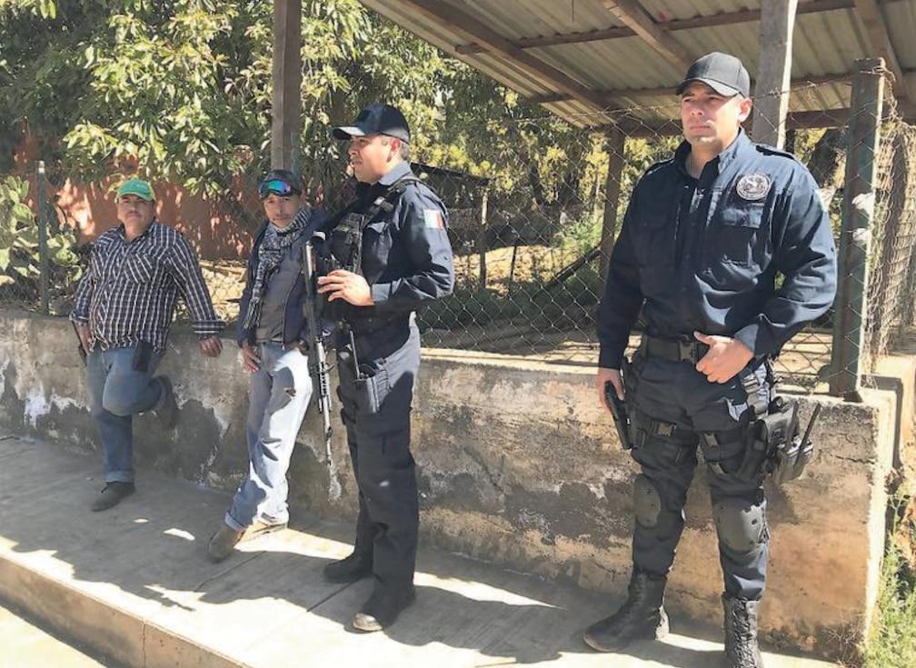 El jefe de policía José Hugo Sánchez Mendoza (izq.) y José Antonio Flores Quezada vigilan el centro de Tancítaro, Michoacán.