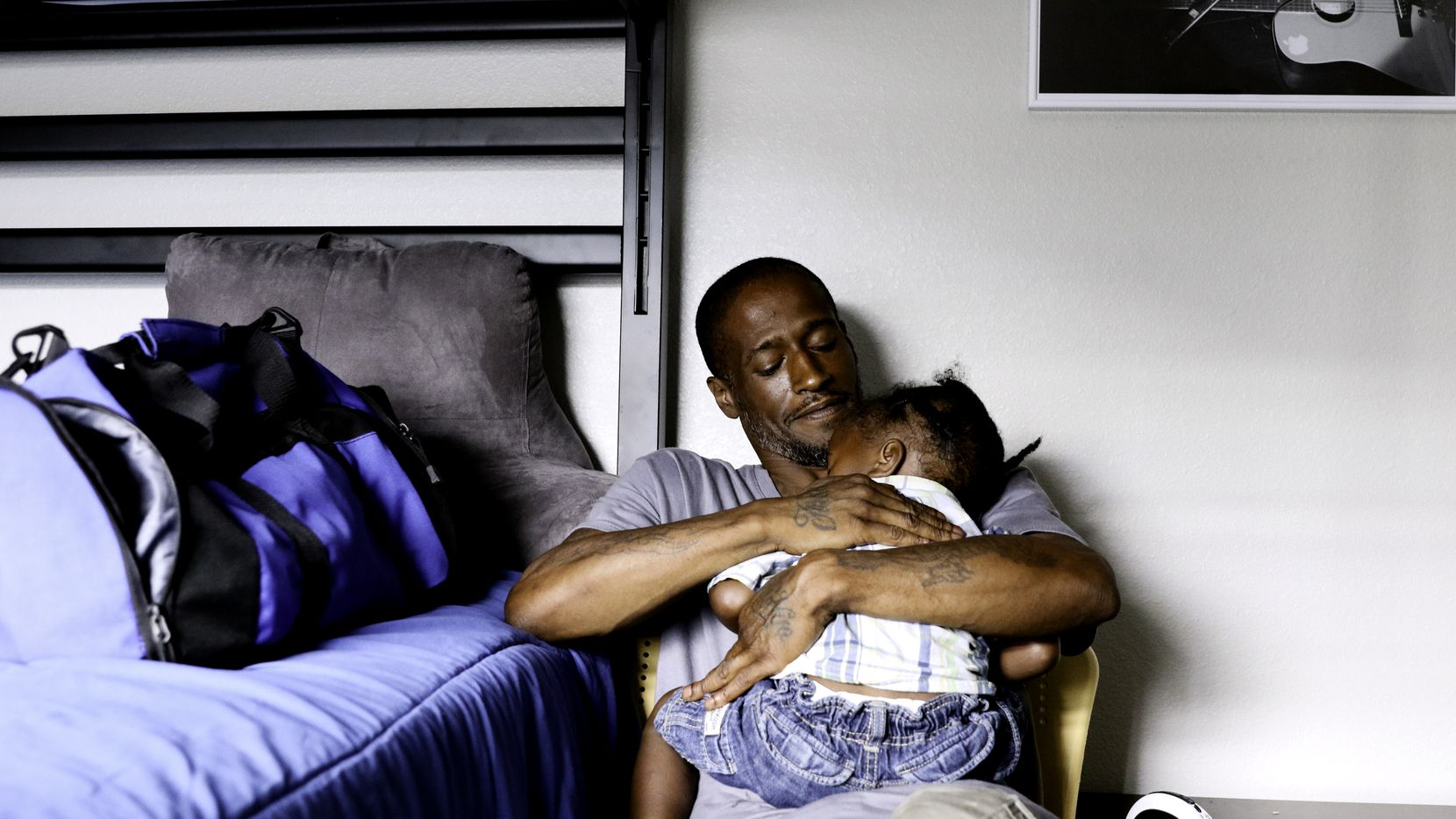 Joshua Miller rocks his son Jordan, 2, to sleep at The Family Place's men's shelter in Dallas. Miller said the new living situation made his son a little anxious, so he likes to be there when he wakes up.