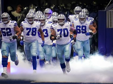 Dallas Cowboys offensive guard Zack Martin (70) leads the team onto the field to face the New York Giants in an NFL football game at AT&T Stadium on Sunday, Oct. 11, 2020, in Arlington.