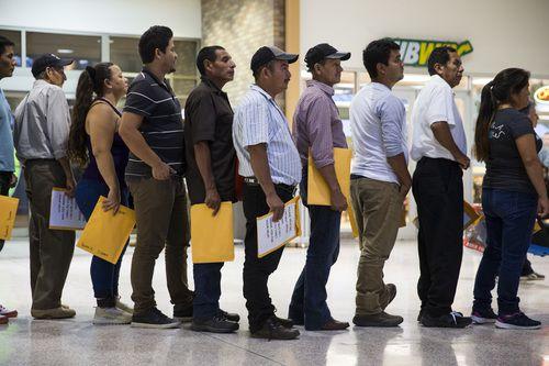 Un grupo de inmigrantes hacen fila para tomar un autobús en McAllen.