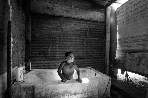 A 3-year-old patiently waits for the dribble of water to reach him in the family's shower, enclosed by hastily built walls of plywood, corrugated tin, and the camper trailer they call home in the Salida Del Sol colonia near Penitas, Texas, in Hidalgo County.