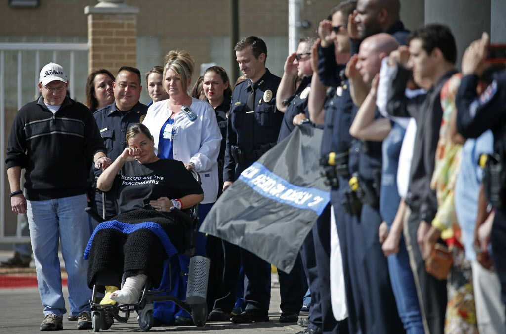 Arlington police officer Cpl. Elise Bowden (in a wheelchair) wipes tears away as police officers salute at the John Peter Smith hospital in Fort Worth, Texas, Sunday, Feb. 5, 2017.