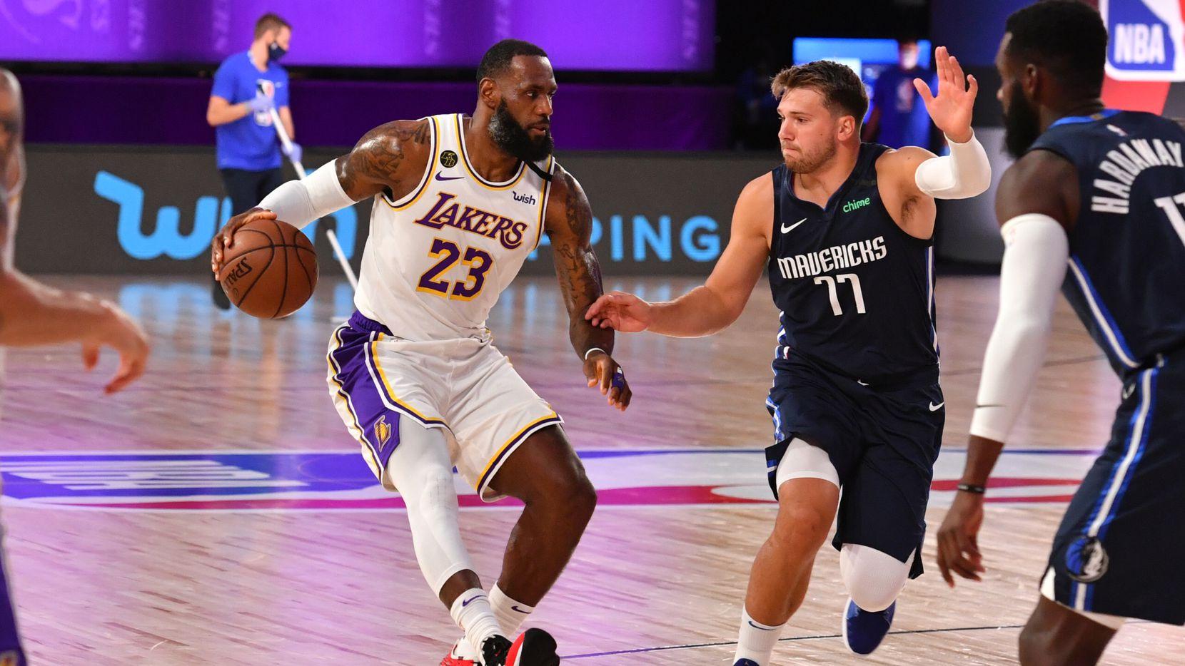 El jugador de los Dallas Mavericks, Luka Doncic (77), custodia al estrella de los Lakers de Los Ángeles, LeBron James, durante el juego de preparación efectuado en Orlando, Florida, el 23 de julio de 2020.