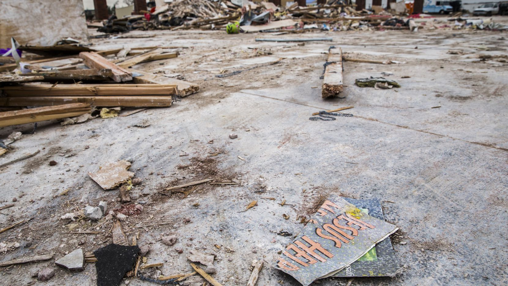 """A pamphlet reading """"Jesus Help"""" lays among the debris at the site of Primera Iglesia Bautista Mexicana on Tuesday in Dallas. The church was destroyed by a tornado last month."""