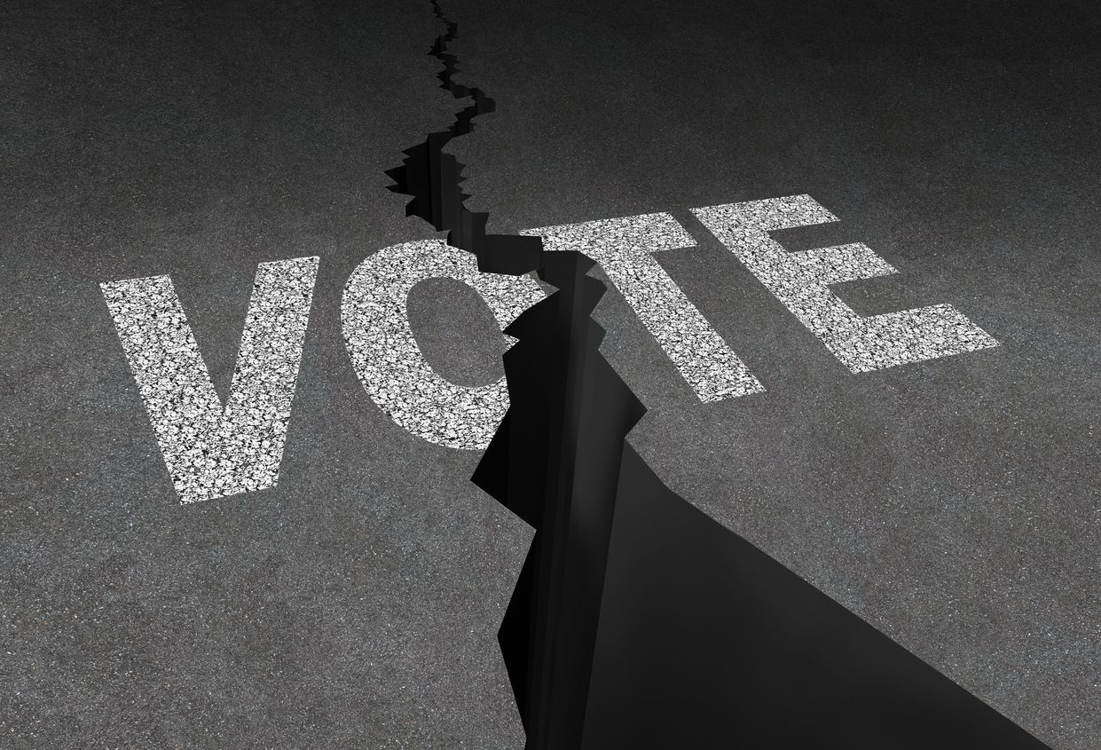 Divided vote concept and split opinion symbol as cracked outdoor asphalt floor with road painted text as a democratic rights metaphor for election crisis or voting corruption.