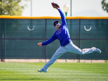 Texas Rangers outfielder Scott Heineman makes a catch while participating in a fielding drill during a spring training workout at the team's training facility on Thursday, Feb. 20, 2020, in Surprise, Ariz.