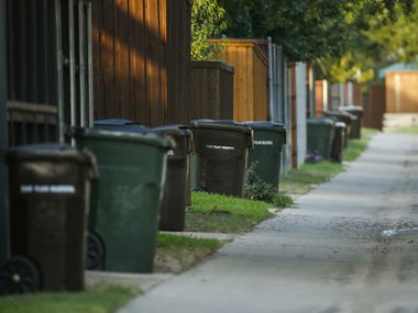 Trash cans line a residential alleyway on Thursday, July 16, 2020 in Plano, Texas. Grand Prairie is asking residents if rolling garbage carts are something they would like in the city.