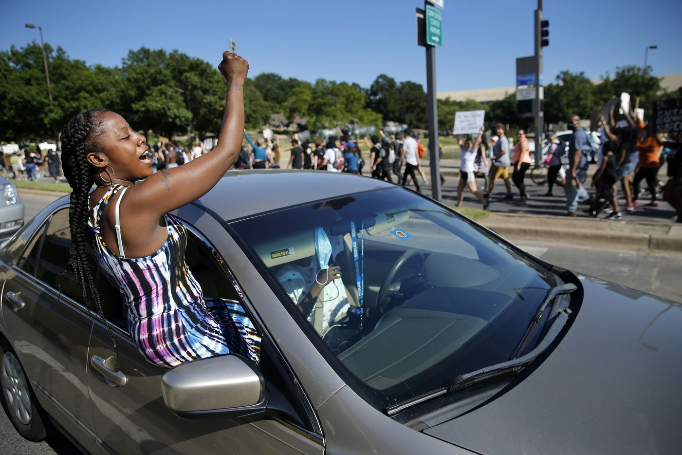 Angel Brown of Dallas crawls out of the car window to support Black Lives Matter supports marching back to Dallas City Hall after a rally in  Dealey Plaza, Wednesday, June 3, 2020. (Tom Fox/The Dallas Morning News)