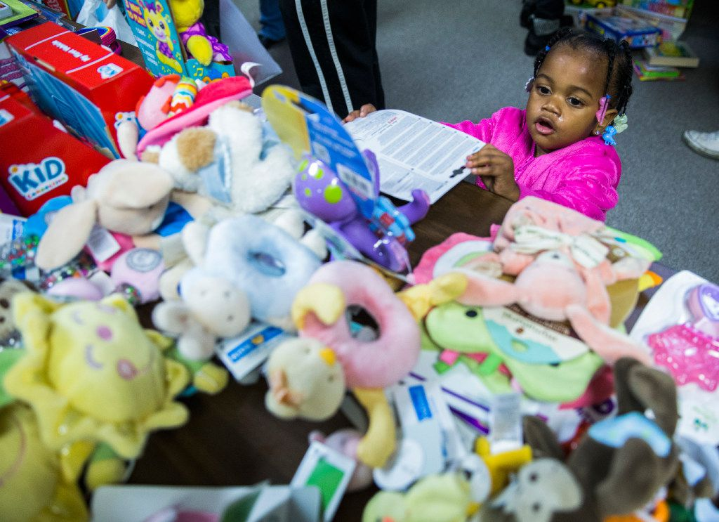 Kennedy Eakles, 1, chooses a toy from a table during The Big Christmas Do-Over in Rowlett.