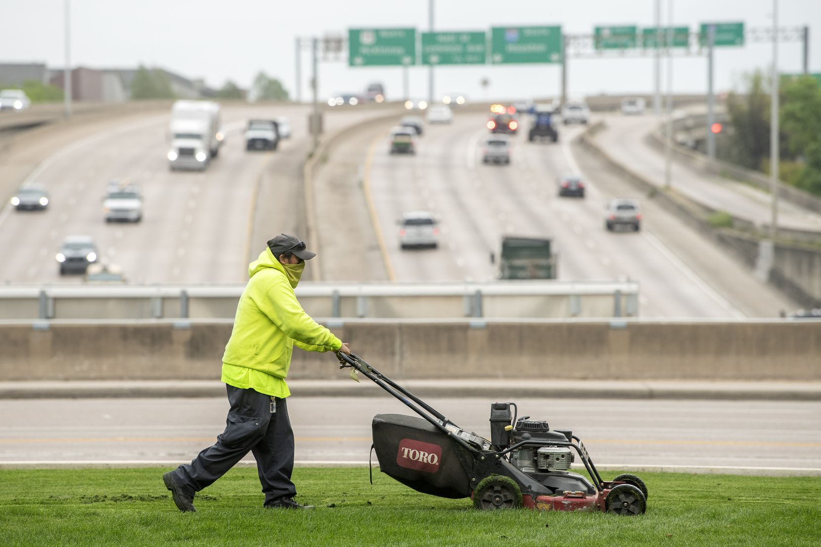 Saul Vasquez, a landscaper with Southern Botanical, mows the grass at Klyde Warren Park.