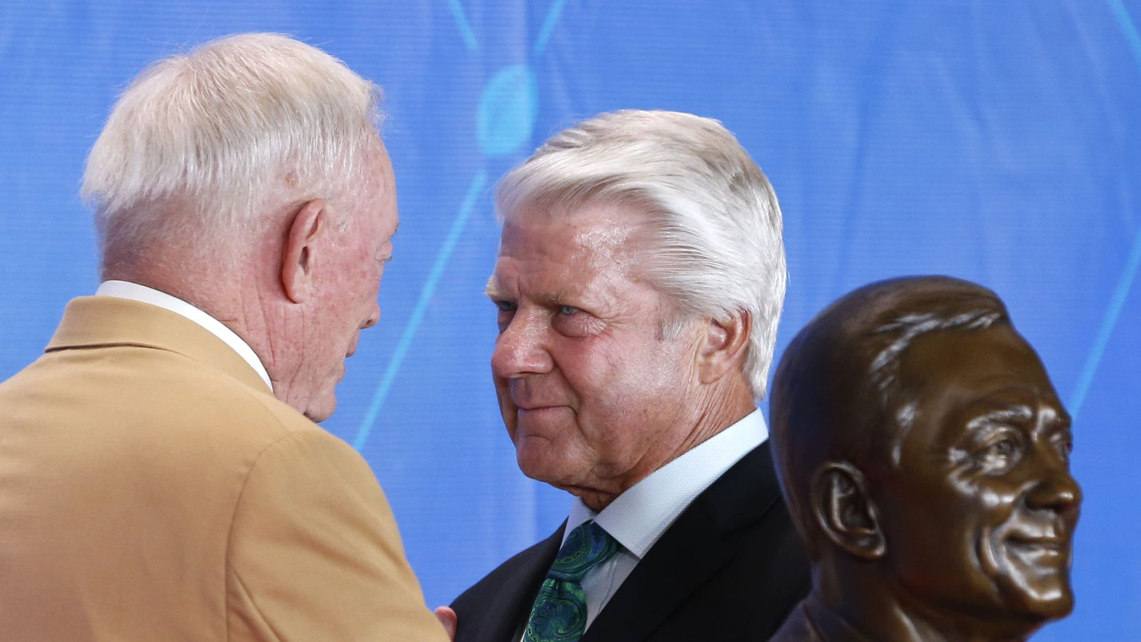 Former Dallas Cowboys head coach Jimmy Johnson listens as 2017 Pro Football Hall of Fame inductee and Dallas Cowboys owner and general manager Jerry Jones talks to him at the 2017 Pro Football Hall of Fame Enshrinement Ceremony at Tom Benson Stadium in Canton, Ohio on Saturday, August 6, 2017.