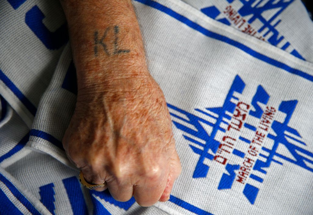"Max Glauben, a Holocaust survivor, shows the words ""KL"" tattoo, which stands in German for concentration camp, ""konzentrationslager,"" with a ""March of the Living"" scarf at his home in 2017."