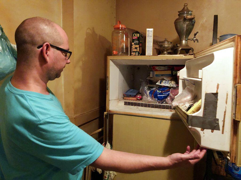 En esta foto del lunes 29 de julio de 2019, Adam Smith se asoma al congelador de su madre en St. Louis, donde dice que encontró los restos de un bebé en una caja y que ella mantuvo allí durante más de 40 años. La madre falleció el 21 de julio, a la edad de 68 años, por cáncer de pulmón. (Christine Byers/St. Louis Post-Dispatch vía AP)