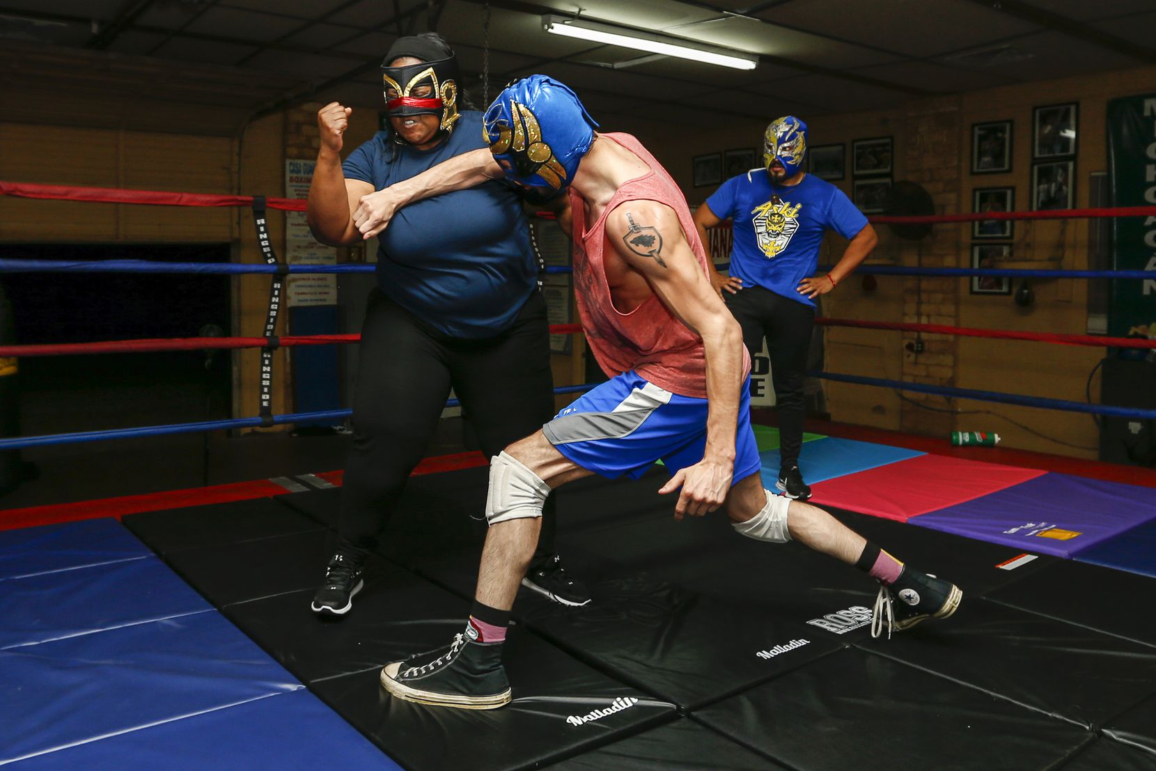 """Dylan Cantu as Huitzi, center, throws a strike towards Tiffany Lang as Coyol as wrestling coordinator Aski watches during a rehearsal of """"Lucha Teotl"""" at Casa Guanajuato."""