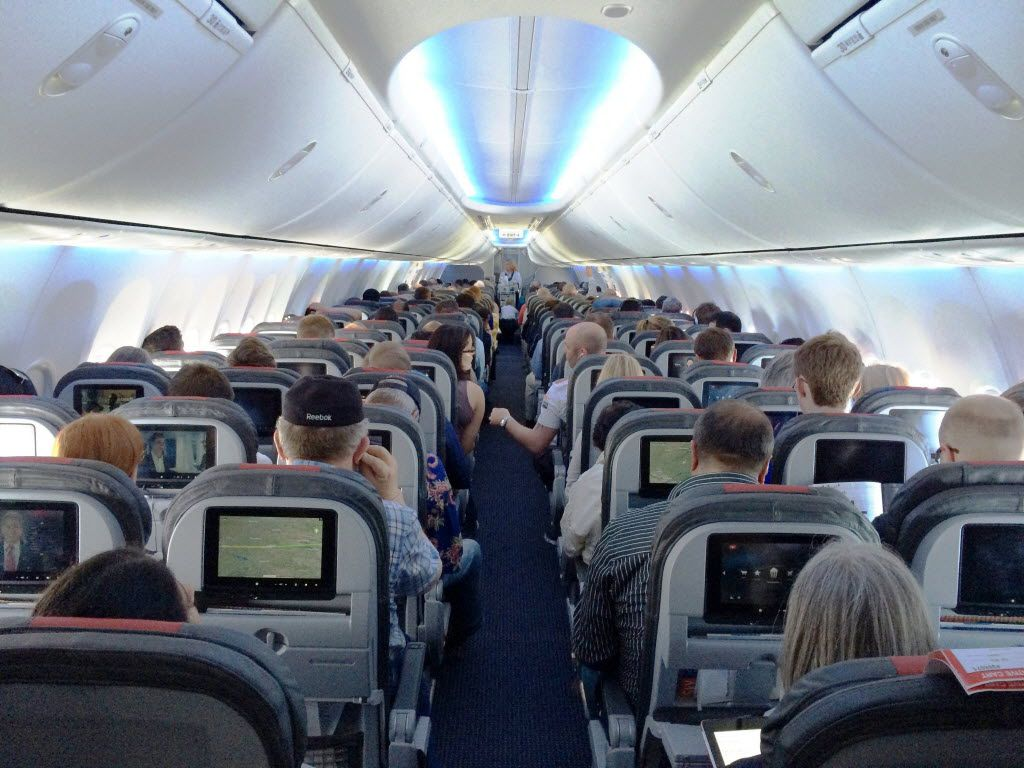 Passenger onboard an American Airlines' new 737s. The cabin gives standard economy passengers less space, but also an entertainment system to distract them.