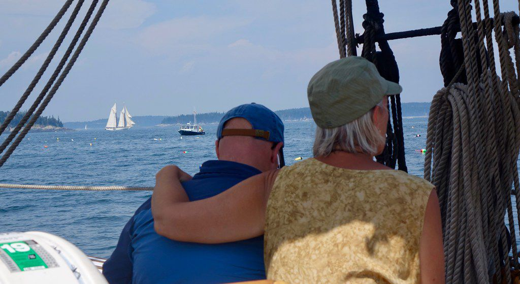 Suzanne Compton and Mike McCrory gaze at the schooner Mary Day, sailing in the background.