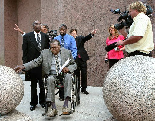 Accompanied by supporters, former Dallas City Council member James Fantroy (front left) leaves the federal courthouse in 2008 without making a statement after his sentencing hearing for stealing more than $20,000 from Paul Quinn College. (FILE PHOTO)