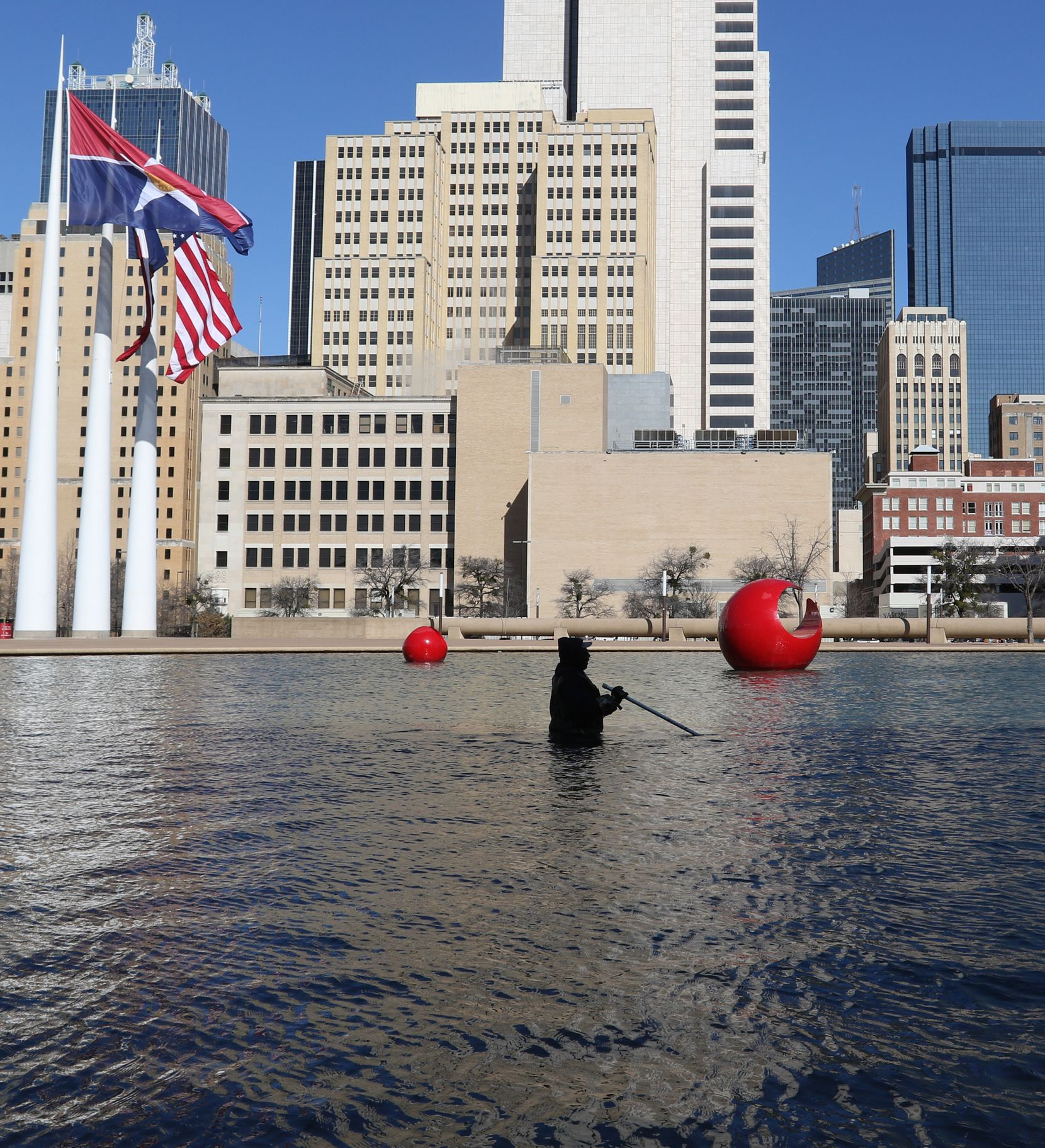 City of Dallas employee Kenneth Argusta cleans the reflecting pool at Dallas City Hall in downtown Dallas, Tuesday, February 12, 2019. (Benjamin Robinson/The Dallas Morning News)