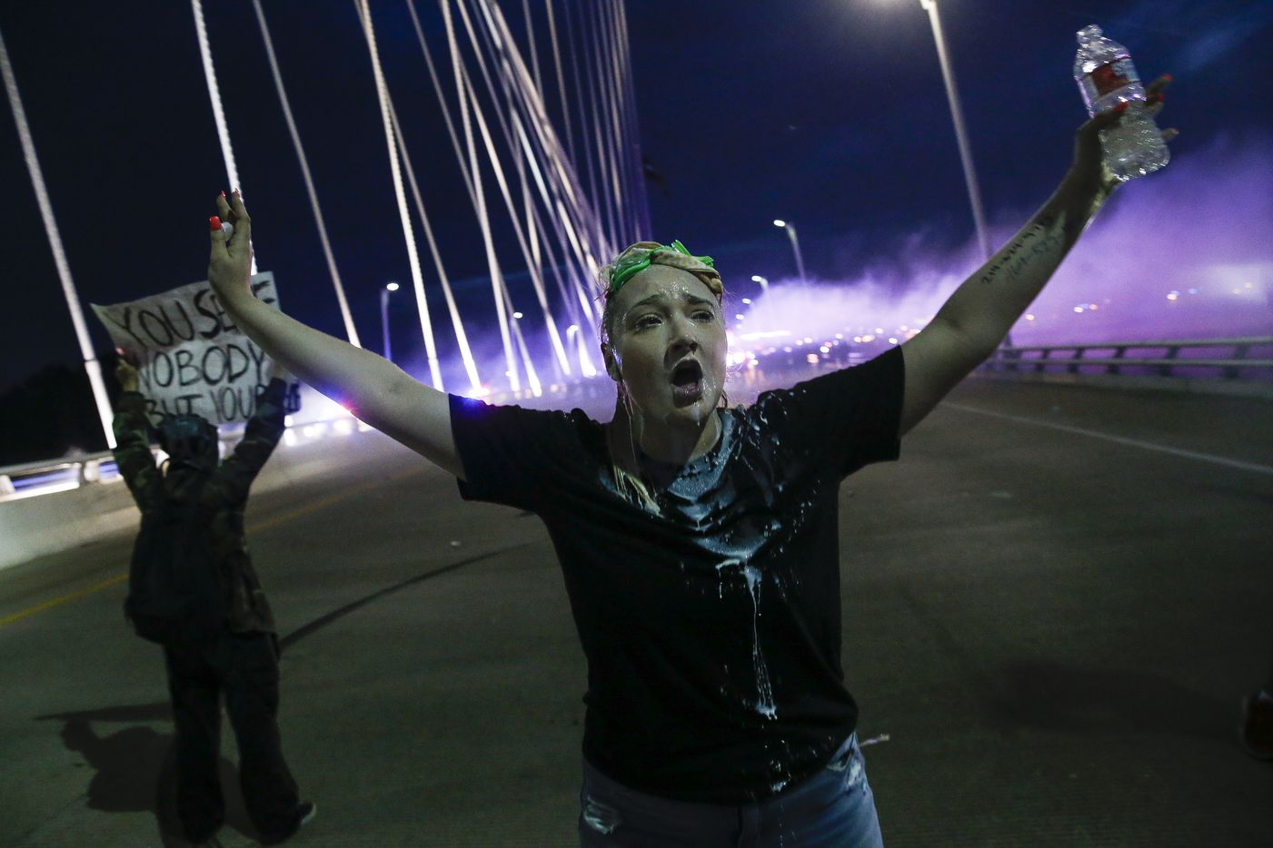 Police deploy smoke bombs and tear gas as they surround protesters who marched onto the Margaret Hunt Hill Bridge while demonstrating against police brutality on Monday, June 1, 2020, in Dallas.The hundreds of protesters were surrounded and detained by police on the bridge and transported to the Dallas County Jail where they were later released.