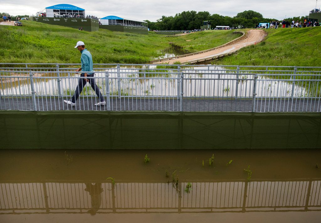 Jordan Spieth crosses a bridge over a flooded low area on his way to hole 7 during round 3 of the Bryon Nelson golf tournament on Saturday, May 11, 2019 at Trinity Forest Golf Club in Dallas. (Ashley Landis/The Dallas Morning News)