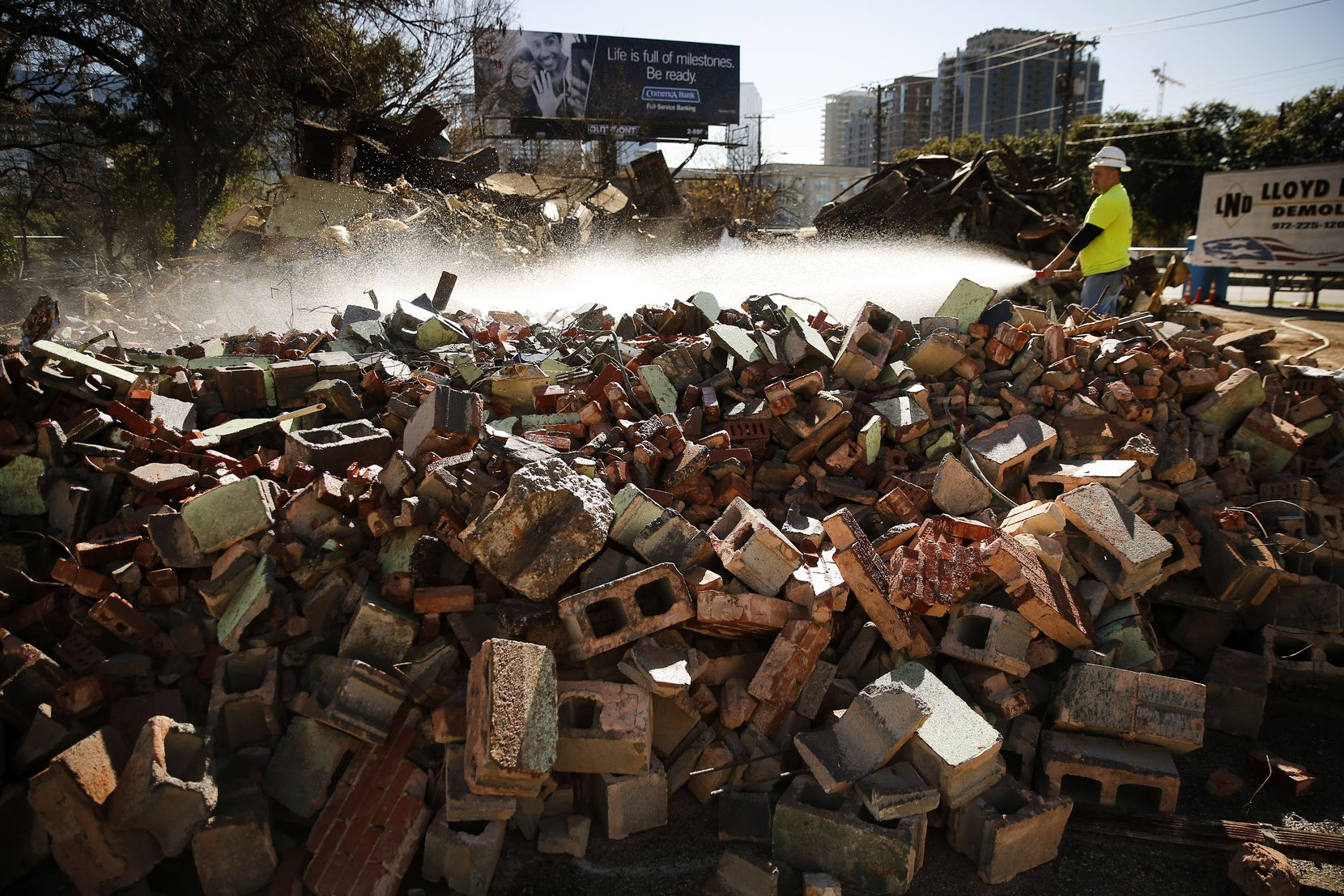 Demolition crewman Alex Robledo sprays water onto a pile of bricks that, until Tuesday, was the Villasana Food Store owned by Charlie Villasana on Harry Hines Boulevard.