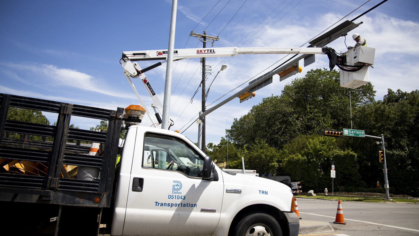 A city employee worked on traffic lights near the Dallas Arboretum and Botanical Garden on Monday, June 10, 2019. A strong storm produced widespread damage throughout Dallas-Fort Worth, causing more than 200,000 people to lose power.