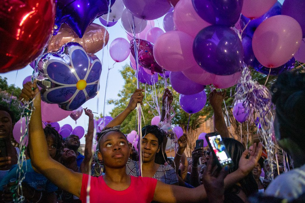 Sontravia Elder (center) prepares to release balloons at a vigil honoring the life of her 9-year-old daughter, Brandoniya Bennett, at the Roseland Townhomes.