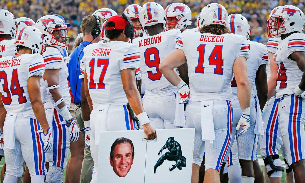 Southern Methodist Mustangs quarterback Austin Upshaw (17) holds a placard containing a photo of Former President George W. Bush on the sidelines during the SMU Mustangs vs. the Michigan Wolverines NCAA football game at Michigan Stadium in Ann Arbor, Michigan on Saturday, September 15, 2018. (Louis DeLuca/The Dallas Morning News)