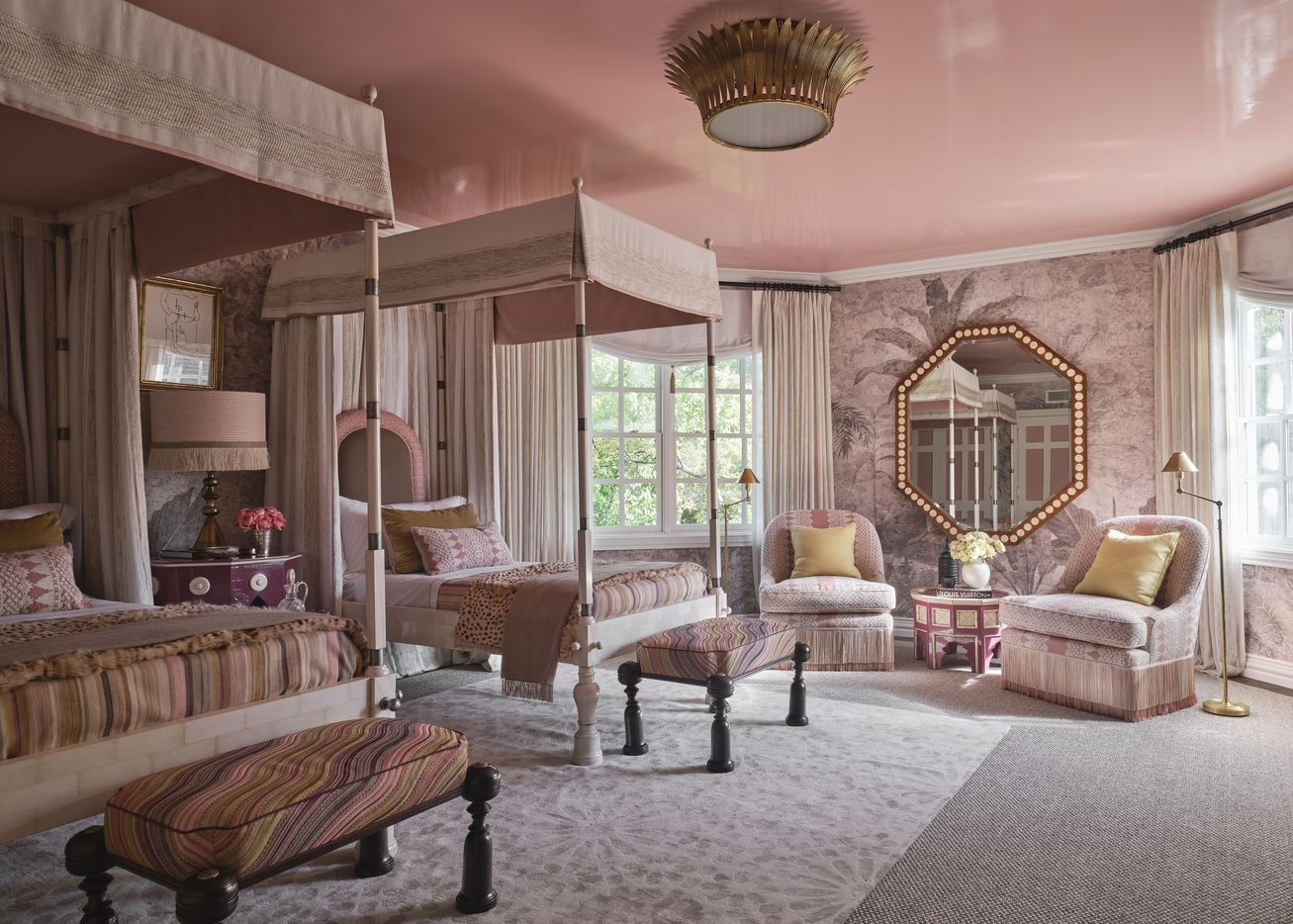 This pink guest bedroom on the second level of the 2021 Kips Bay Decorator Show House Dallas was designed by Martyn Lawrence Bullard Design. The room has pink hues, patterned fabrics, an antique Indian armoire and other design details sourced from around the world.