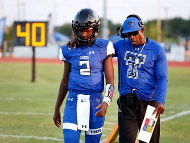 Trinity Christian-Cedar Hill offensive coordinator Deion Sanders (right) talks to his son, Shedeur Sanders, before a game in 2017.